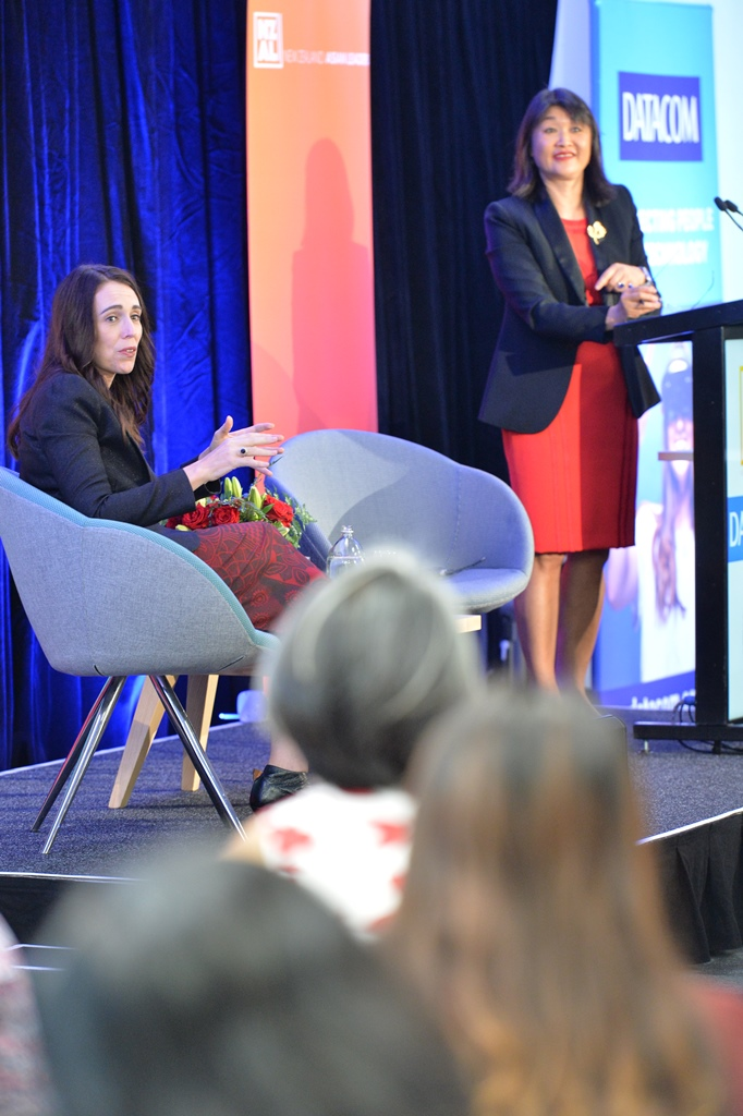 Jacinda Ardern speaks to the audience while Mai Chen looks on from the podium